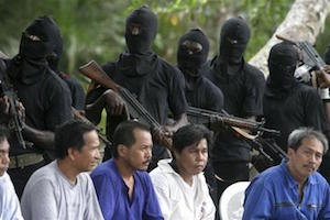 Some hostages of the Philippines sit as they are guarded by militants of MEND at an undisclosed location on the creeks of Niger delta